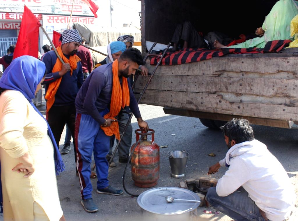 Barred from Delhi: Farmers put up tents, make food at Singhu.