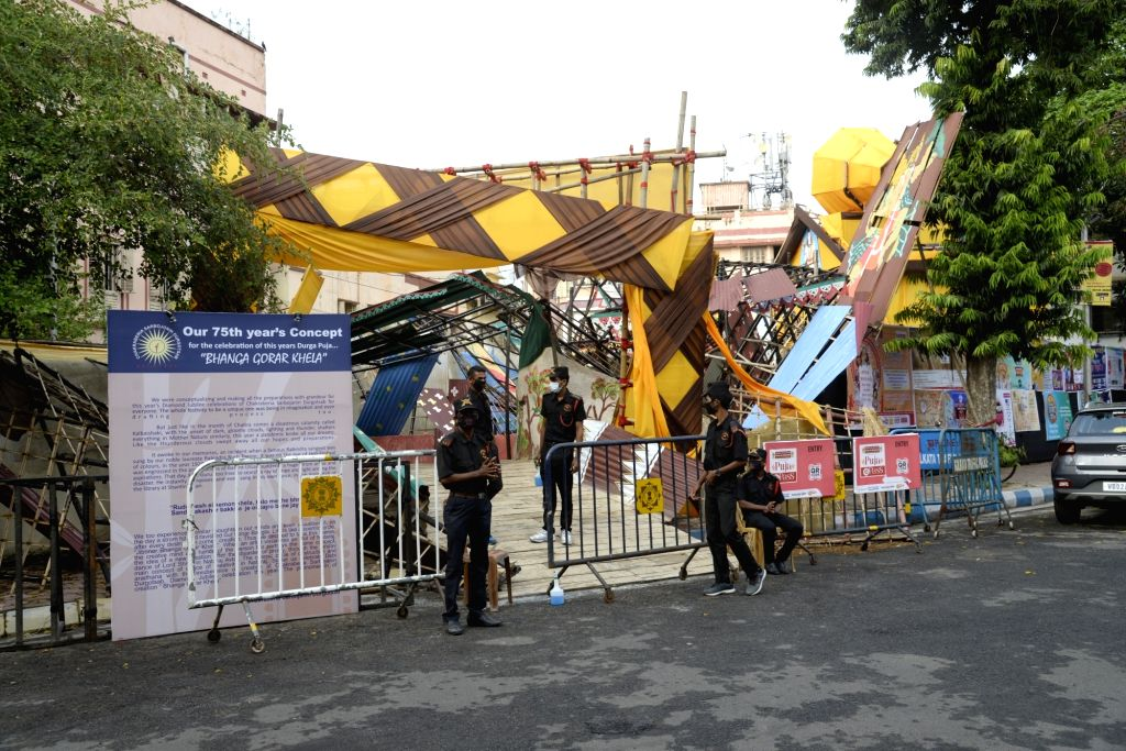 Barricades put up and security personnel sit outside the Chakraberia Sarbojanin community puja pandal ahead of Durga Puja celebrations, in Kolkata on Oct 19, 2020. This comes close on the ...
