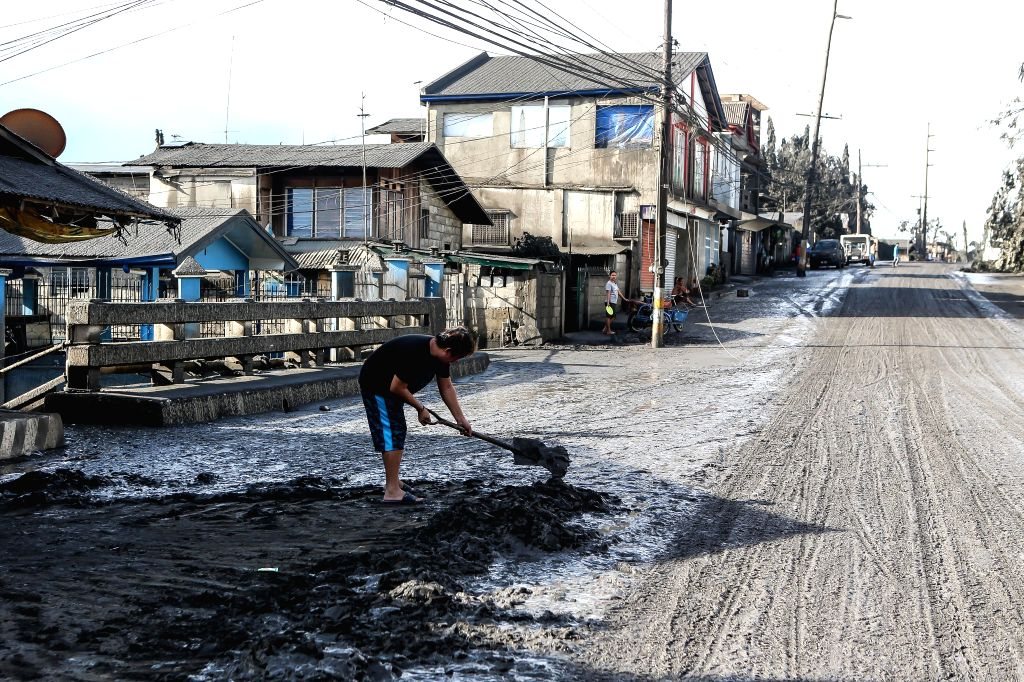 BATANGAS, Jan. 13, 2020 (Xinhua) -- A resident clears an ash and mud covered road as Taal Volcano erupts in Batangas Province, the Philippines, Jan. 13, 2020. Nearly 50,000 people living near the volcano on an island close to the Philippine capital h