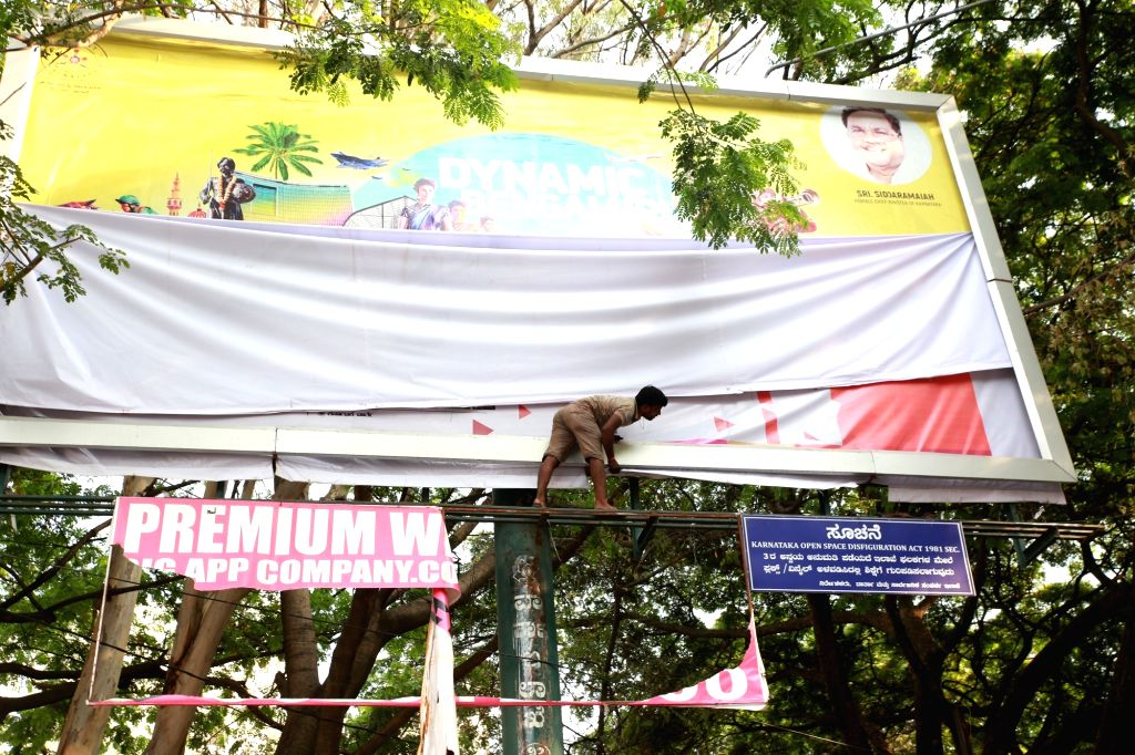 BBMP workers remove banners and flex of political leaders after the announcement dates of assembly election date in Bengaluru, on March 27, 2018.