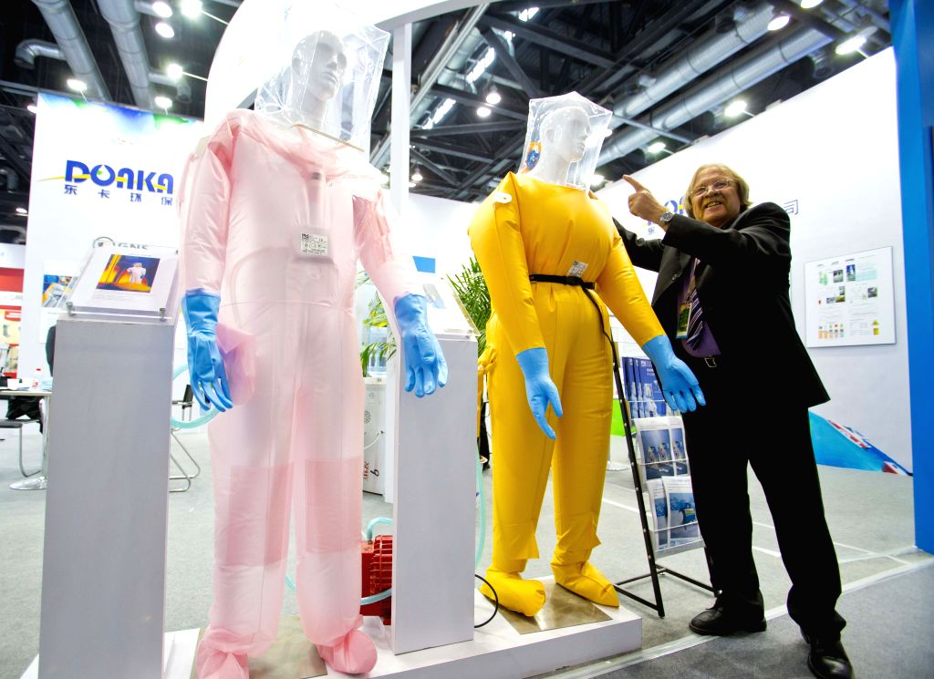 "A staff member shows protective suits at the exhibition ""Nuclear Industry China 2014"" in Beijing, China, April 15, 2014. The four-day exhibition kicked .."