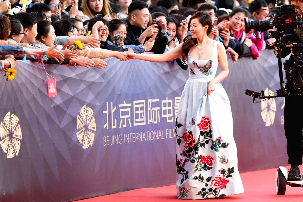 BEIJING, April 16, 2016 - Singer Zhang Liangying shakes hands with fans as she attends a red carpet event held for the opening ceremony of the 6th Beijing International Film Festival (BJIFF) in ...