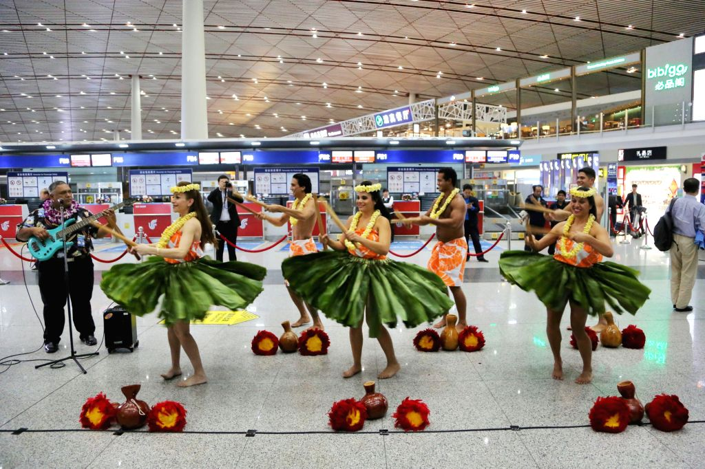 Performers dance to celebrate the opening of Honolulu-Beijing direct flights by Hawaiian Airlines at the Beijing Capital International Airport in Beijing, capital .
