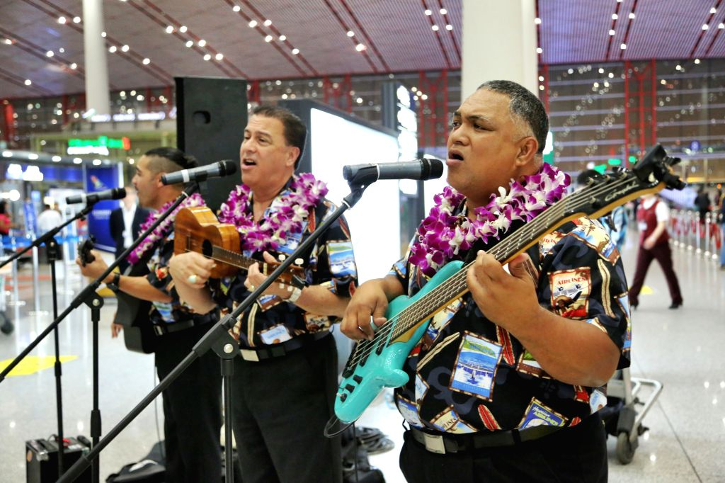 Performers sing to celebrate the opening of Honolulu-Beijing direct flights by Hawaiian Airlines at the Beijing Capital International Airport in Beijing, capital ..
