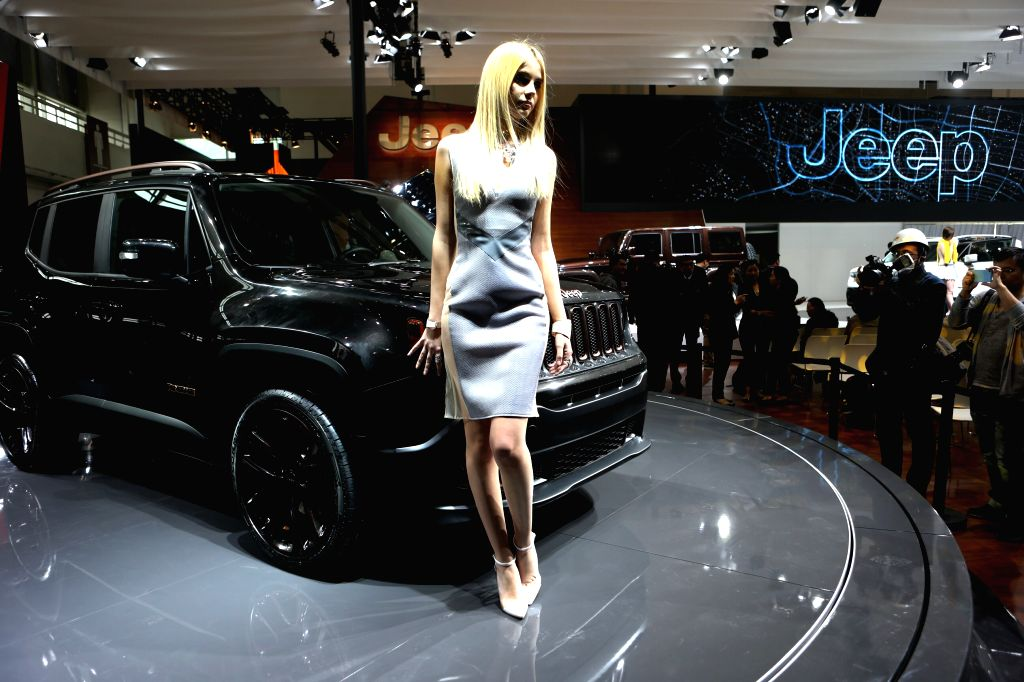 A model presents an automobile during a rehearsal at the Jeep exhibition area in Beijing, capital of China, April 19, 2014. The 13th Beijing Automotive Exhibition .
