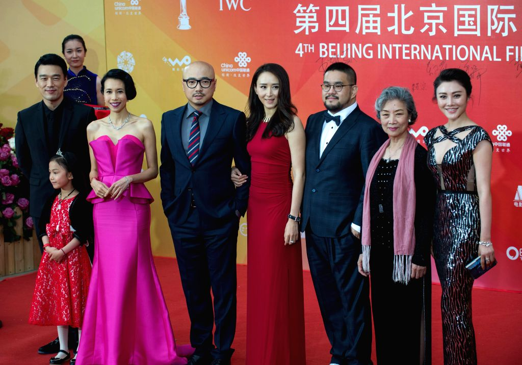 """Cast members of the movie """"The Great Hypnotist"""" pose at the red carpet during the closing ceremony of the 4th Beijing International Film Festival in ..."""