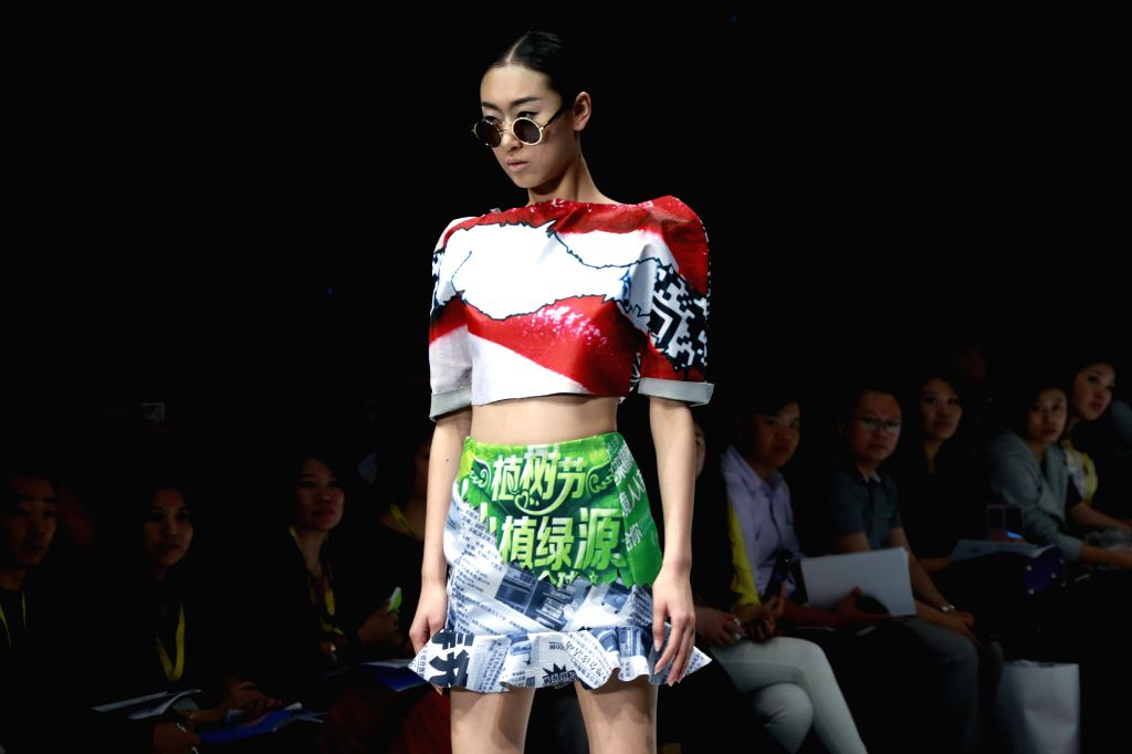 A model presents a creation designed by graduates from Guangzhou University College of Textile and Garment during the 2014 China Graduate Fashion Week in Beijing, .
