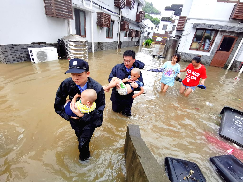 BEIJING, Aug. 11, 2019 - Policemen transfer the flood-stranded people in Putuo scenic area of Zhoushan City, east China's Zhejiang Province, Aug. 10, 2019.