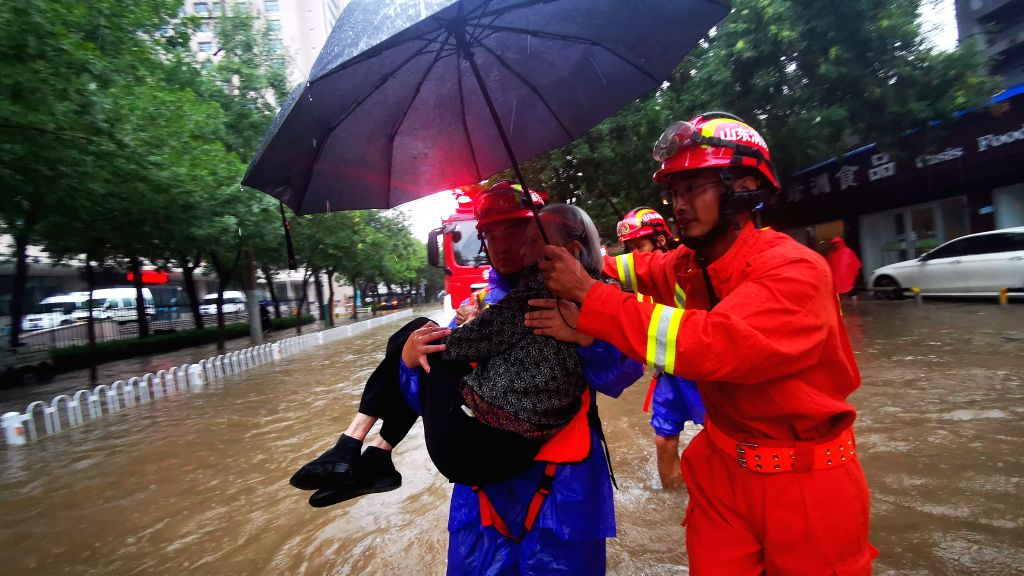 BEIJING, Aug. 11, 2019 - Rescuers help a flood-stranded elderly woman in Binzhou, east China's Shandong Province, Aug. 11, 2019.