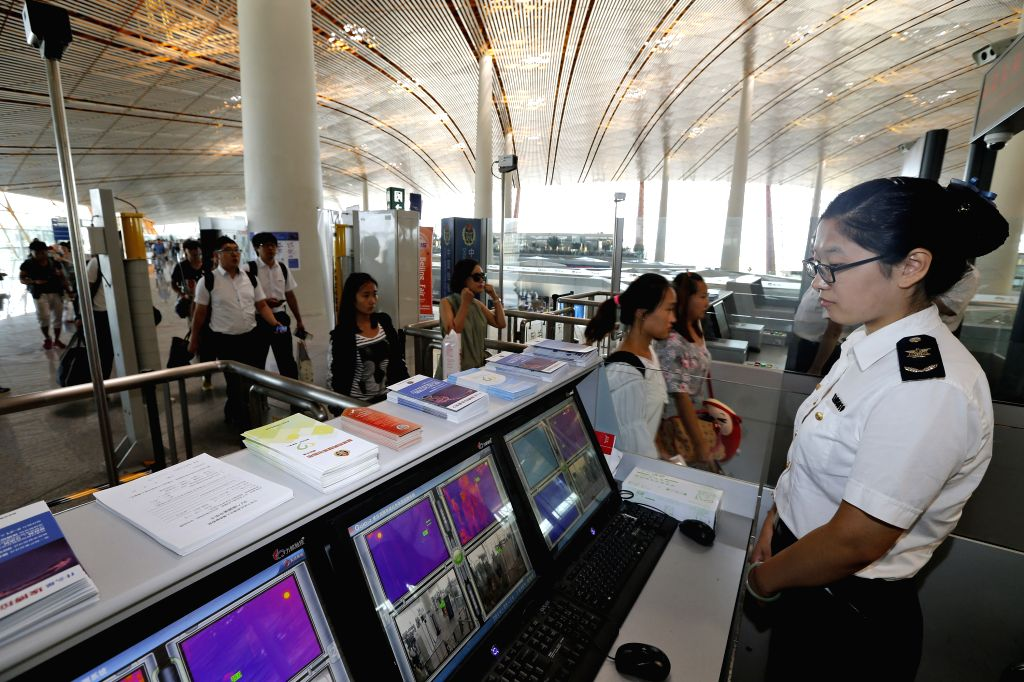 A quarantine staff member monitors body temperatures of passengers who pass infrared thermometry machine at Beijing Capital International Airport in Beijing, ...