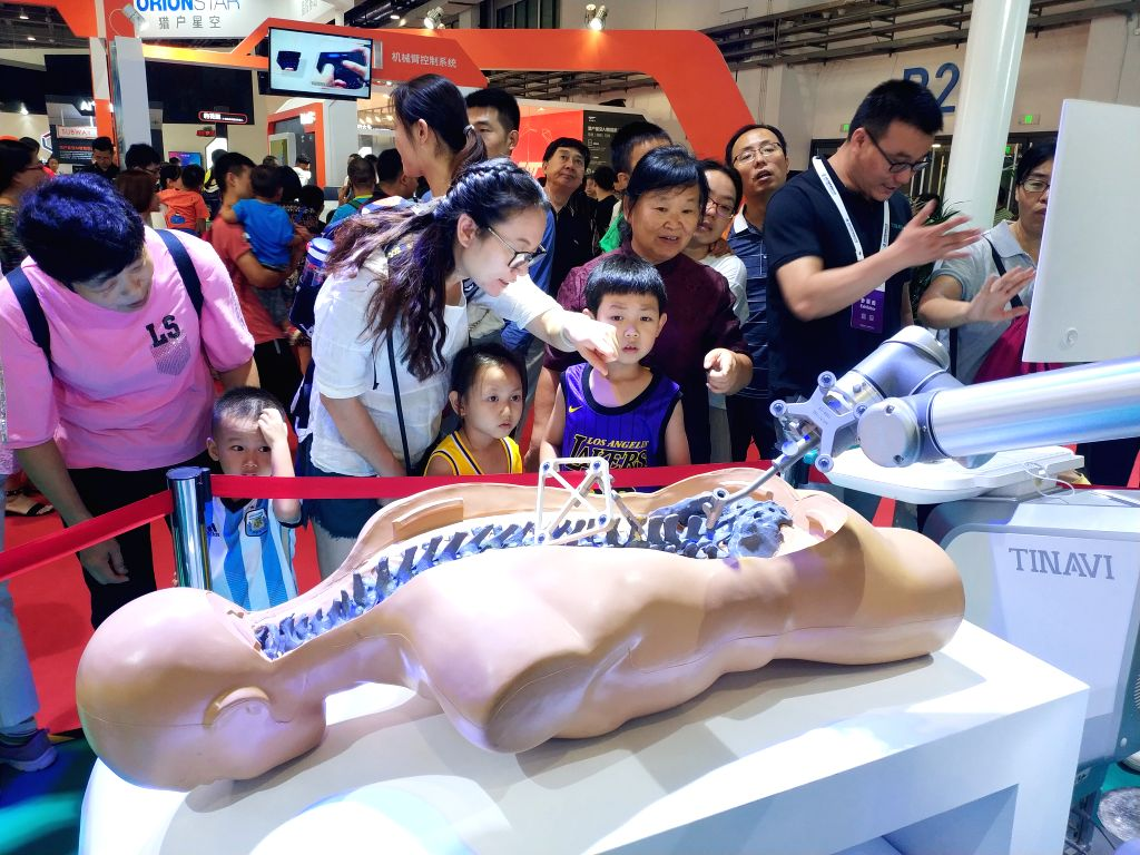 BEIJING, Aug. 25, 2019 - Mobile photo shows people visiting the World Robot Exhibition in Beijing, capital of China, Aug. 24, 2019.