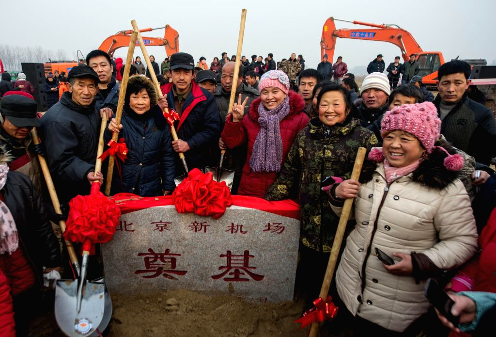 Local villagers pose with the foundation stone at the ground breaking ceremony of Beijing's new airport in the Daxing District of Beijing, capital of China, Dec. ...