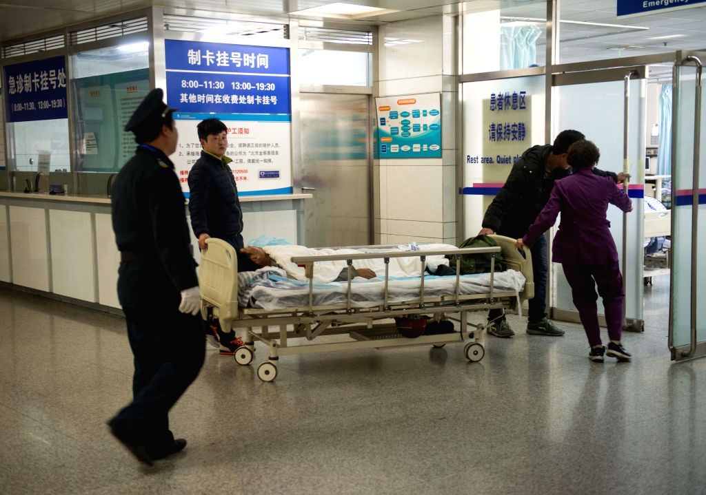 A man injured in a scaffold collapse is wheeled to a ward of the Haidian Hospital in Beijing, China, Dec. 29, 2014. Ten workers were killed and four were injured ...