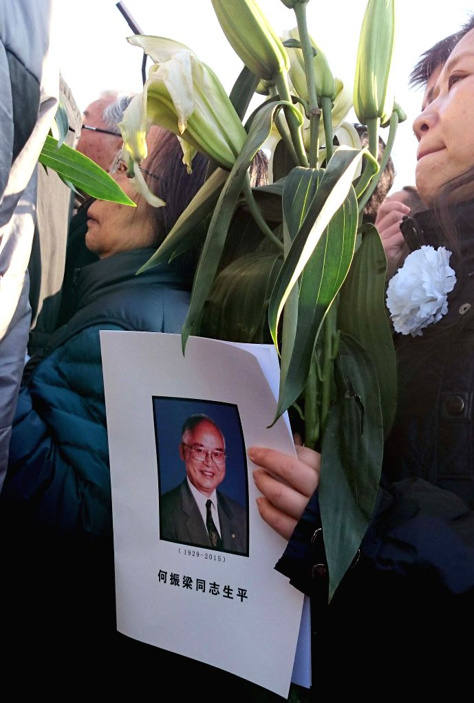 A woman holds the picture of He Zhenliang, former International Olympic Committee (IOC) member and vice president, during a farewell ceremony for He Zhengliang at ..