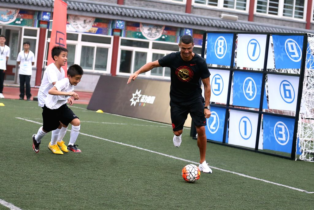 BEIJING, July 19, 2018 - Portuguese football player Cristiano Ronaldo plays football with students as he attends a promotional event in Beijing, China, on July 19, 2018.