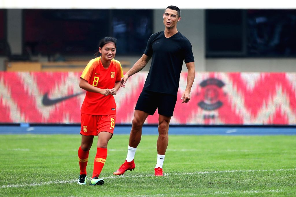 BEIJING, July 20, 2018 - Portuguese football player Cristiano Ronaldo (R) instructs a young player shooting as he attends a promotional event in Beijing, China, on July 20, 2018.