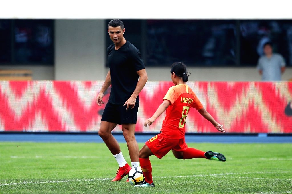 BEIJING, July 20, 2018 - Portuguese football player Cristiano Ronaldo (L) instructs a young player shooting as he attends a promotional event in Beijing, China, on July 20, 2018.