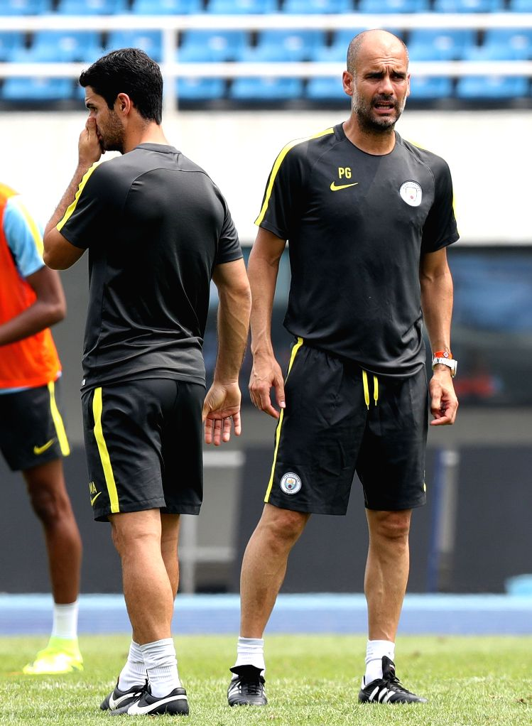 BEIJING, July 24, 2016 - Pep Guardiola (R), manager of Manchester City talks with his team member, former Arsenal's player Mikel Arteta during the training session for the match against Manchester ...