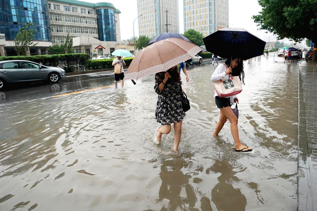 BEIJING, July 24, 2018 - Pedestrians walk in rain on a waterlogged road in Chaoyang District in Beijing, capital of China, July 24, 2018.  Beijing issued a yellow warning for heavy rain on Tuesday ...