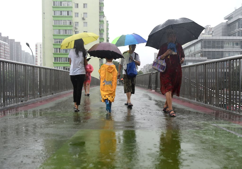 BEIJING, July 24, 2018 - Pedestrians walk in rain on an overpass in Beijing, capital of China, July 24, 2018.  Beijing issued a yellow warning for heavy rain on Tuesday morning.