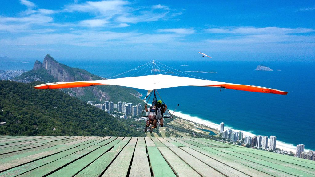 BEIJING , Jun. 16, 2016 - This file photo shows gliding enthusiasts flying with a delta wing from a platform located at the Pedra Bonita of Mountain Gavea in Rio de Janeiro, Brazil on Feb. 10, 2015. ...