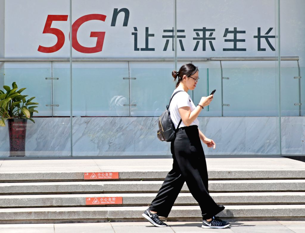 BEIJING, June 3, 2019 (Xinhua) -- A woman walks past a billboard of 5G in Beijing, capital of China, June 3, 2019. China will soon grant 5G licenses for commercial use, the country's Ministry of Industry and Information Technology said Monday. The se