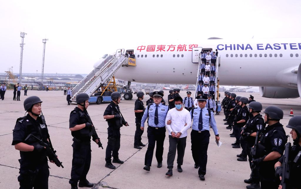 BEIJING, June 7, 2019 - The police escort suspects to disembark from a plane at Capital International Airport in Beijing, capital of China, June 7, 2019. A group of 94 suspects, escorted by Chinese ...