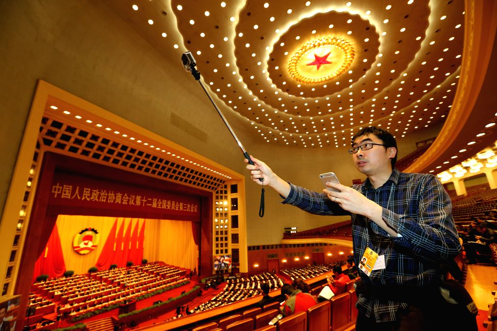 A photographer takes photos with a GoPro during the third plenary meeting of the third session of the 12th National Committee of the Chinese People's Political ...