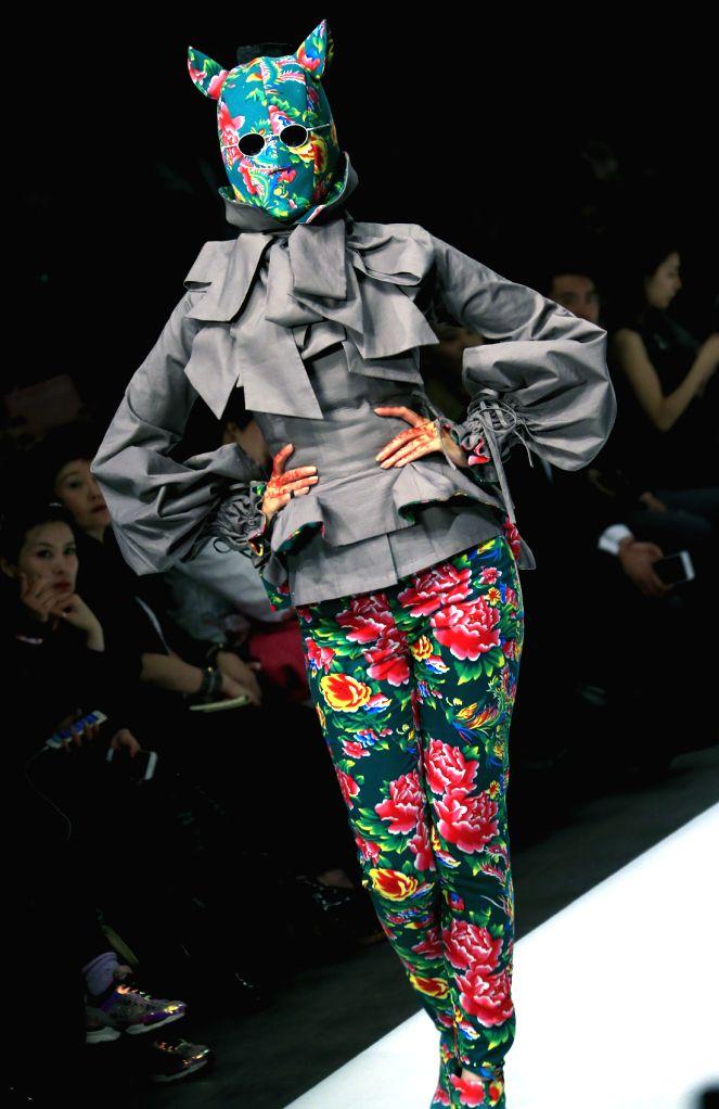 A model presents a creation of Sheguang Hu during the China Fashion Week Autumn/Winter 2015/2016 in Beijing, capital of China, March 25, 2015. (Xinhua/Li ...