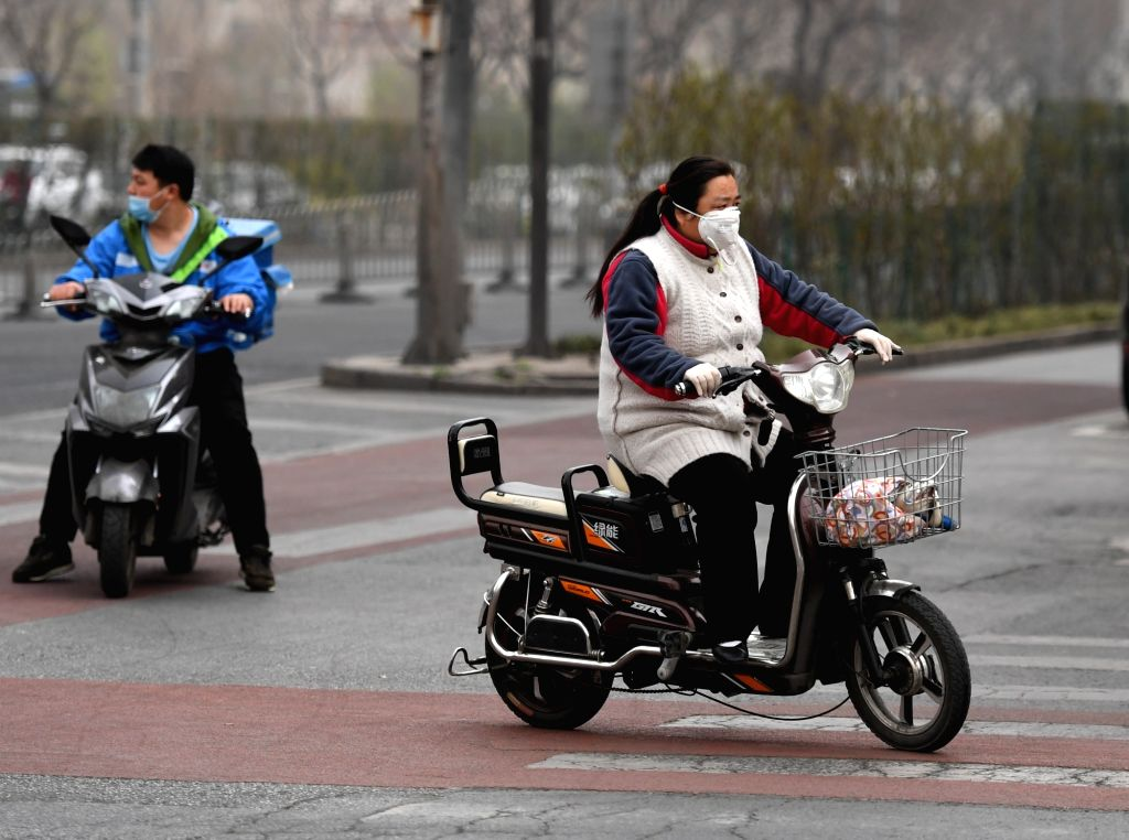 BEIJING, March 28, 2018 - Citizens ride against floating dust and sand in Beijing, capital of China, March 28, 2018. Floating dust hit Beijing on Wednesday.