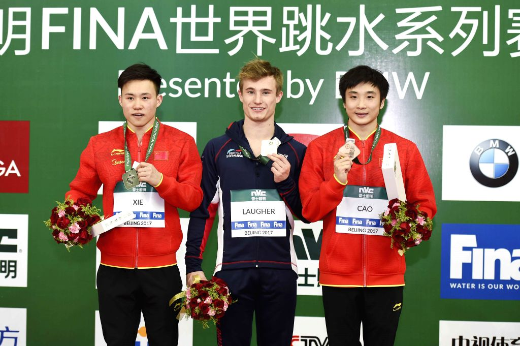 BEIJING, March 4, 2017 - Silver medalist Xie Siyi of China, gold medalist Jack Laugher of Britain and bronze medalist Cao Yuan of China (L to R) react during the awarding ceremony for men's 3m ...