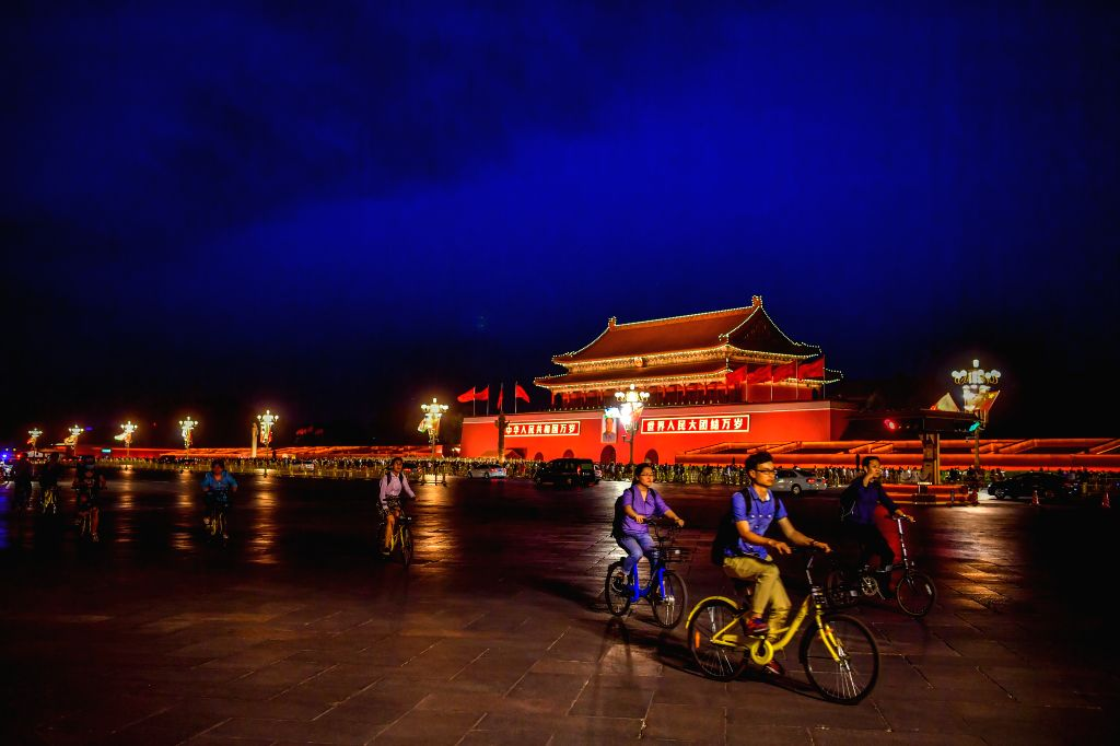 BEIJING, May 13, 2017 - People ride past the Tian'anmen Rostrum in downtown Beijing, capital of China, May 12, 2017. Landscape lighting will illuminate Beijing in the evening from May 12 to 17 as in ...