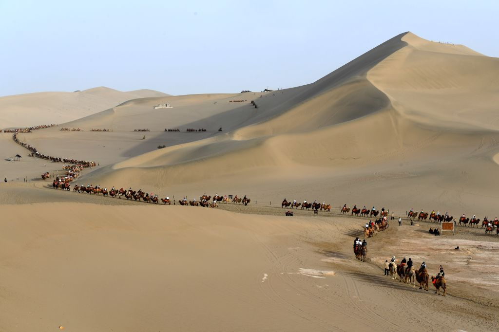 BEIJING, May 6, 2019 - Tourists ride camels in the Crescent Spring and Mingsha Sand Dune scenic area in Dunhuang, northwest China's Gansu Province, on May 1, 2019. Tourists logged 195 million ...