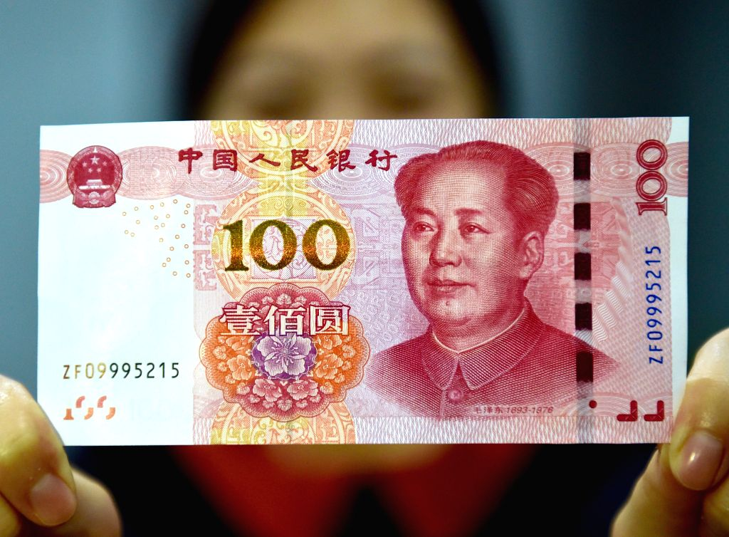 BEIJING, Nov. 12, 2015 (Xinhua) -- A resident displays a new 100-yuan banknote in Beijing, capital of China, Nov. 12, 2015. China's central bank released a new 100-yuan banknote on Thursday. The design stays largely the same as its former series, but