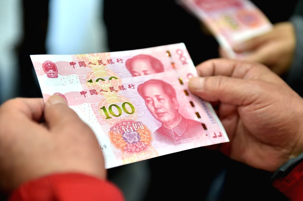 BEIJING, Nov. 12, 2015 (Xinhua) -- Residents hold two new 100-yuan banknotes withdrawn from the Beijing Branch of the Bank of Communication in Beijing, capital of China. China's central bank released a new 100-yuan banknote on Thursday. The design st