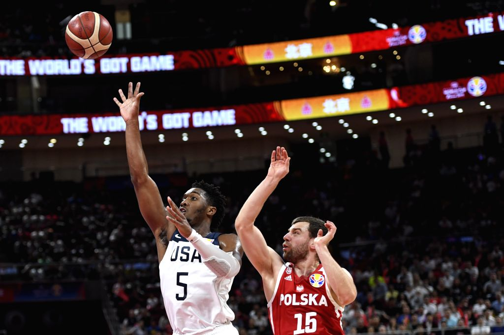 BEIJING, Sept. 14, 2019 - Donovan Mitchell (L) of the United States shoots beside Kamil Laczynski of Poland during the Classification Games 7-8 between the United States and Poland at the 2019 FIBA ...