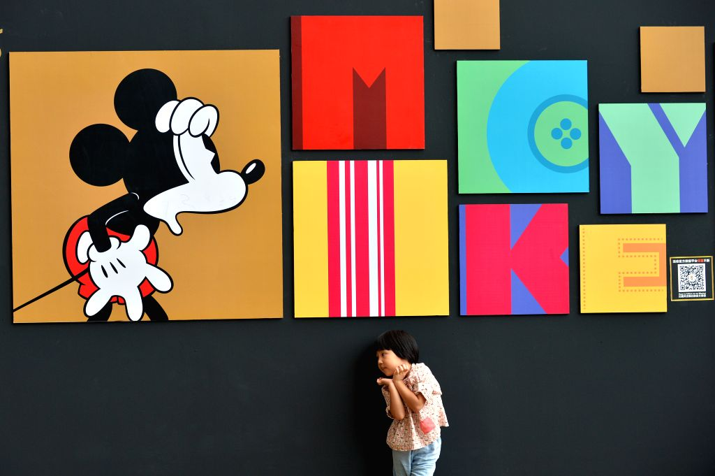 A child plays in front of a wall presenting Disney figure Mickey at the Walt Disney 90th Anniversary Exhibition in Indigo Department Store in Beijing, capital of ...