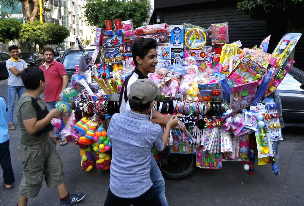 BEIRUT, Aug. 11, 2019 - Children play in front of a toy stall during the Eid al-Adha holiday in Beirut, Lebanon, on Aug. 11, 2019.