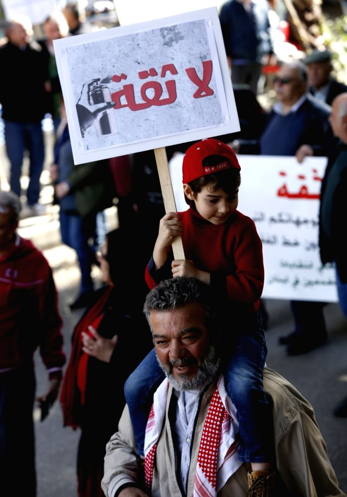 BEIRUT, Feb. 17, 2019 - A boy holds a banner during a protest in Beirut, capital of Lebanon, Feb. 17, 2019. Hundreds of Lebanese on Sunday protested in capital Beirut's downtown against the new ...