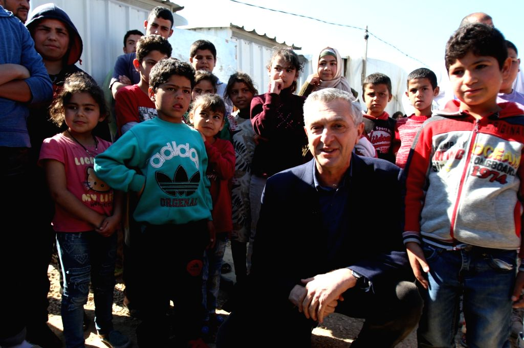 BEIRUT, March 10, 2019 - Filippo Grandi (2nd R, front), United Nations High Commissioner for Refugees, poses for photos with children at a Syrian refugee camp in northern Lebanon's Akkar, March 9, ...