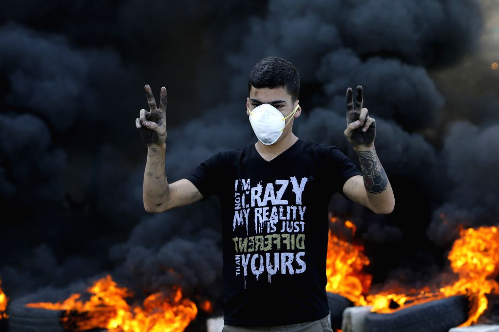 BEIRUT, Nov. 13, 2019 - A protest gestures in front of burning tyres in Khaldeh, south of Lebanon, on Nov. 13, 2019. Thousands of Lebanese demonstrators blocked streets all over Lebanon on Wednesday ...