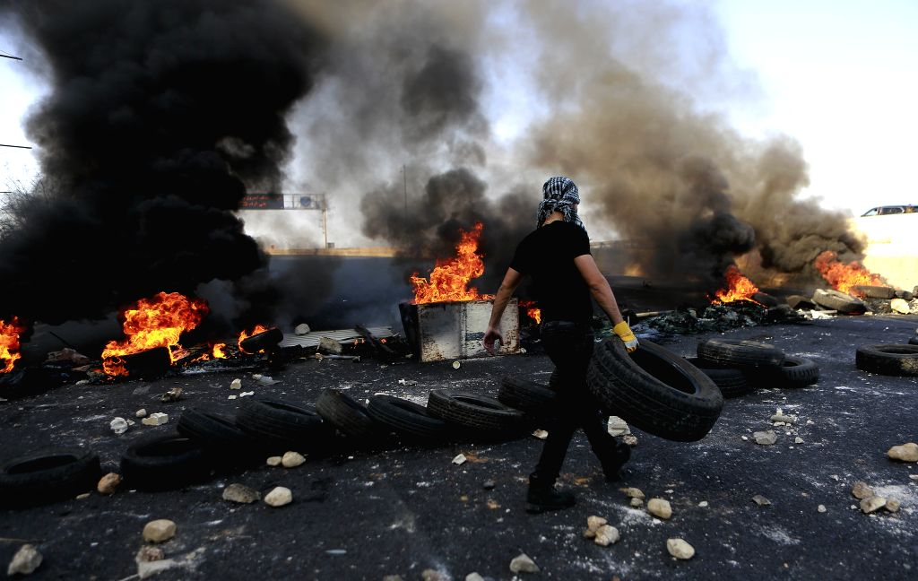 BEIRUT, Nov. 13, 2019 - Protesters burn tyres to block the road in Nahr el Kalb, north of Beirut, Lebanon, on Nov. 13, 2019. Thousands of Lebanese demonstrators blocked streets all over Lebanon on ...