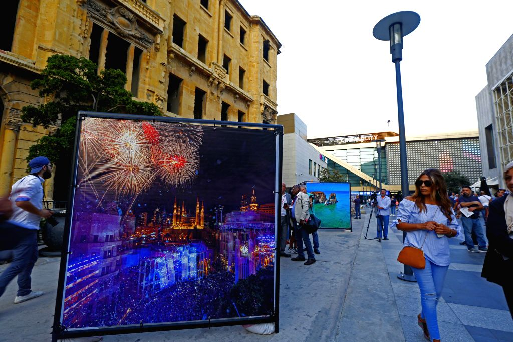 BEIRUT, Sept. 4, 2019 - People walk past a photo work during the opening exhibition of the Beirut Image Festival 2019 in Beirut, Lebanon, on Sept. 4, 2019. The Beirut Image Festival 2019 kicked off ...