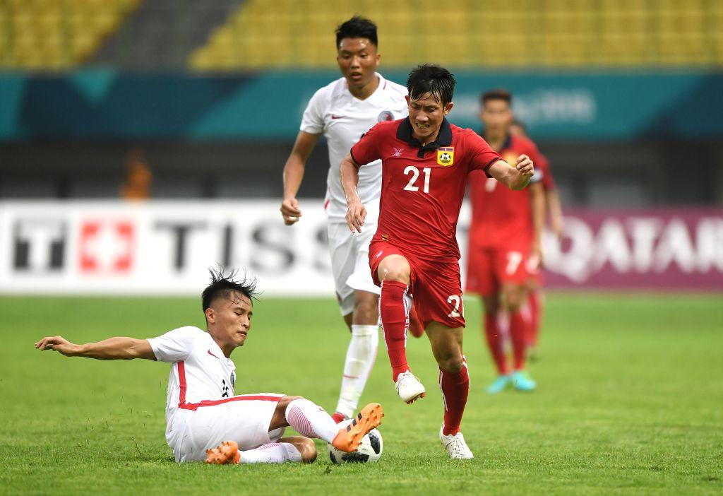 BEKASI, Aug. 10, 2018 - Yu Pui Hong (L) of Hong Kong of China vies with Bounmalay Tiny of Laos during the Men's Football Group A match between Hong Kong of China and Laos at the 18th Asian Games at ...