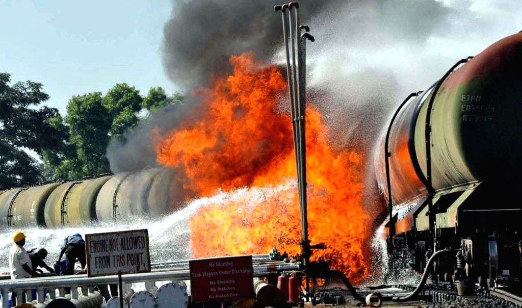 Fire fighters try hard to douse a fire that broke out in an oil wagon rake belonging to Indian Oil while transferring fuel in a depot at Belagavi, Karnataka on Jan 10, 2015.