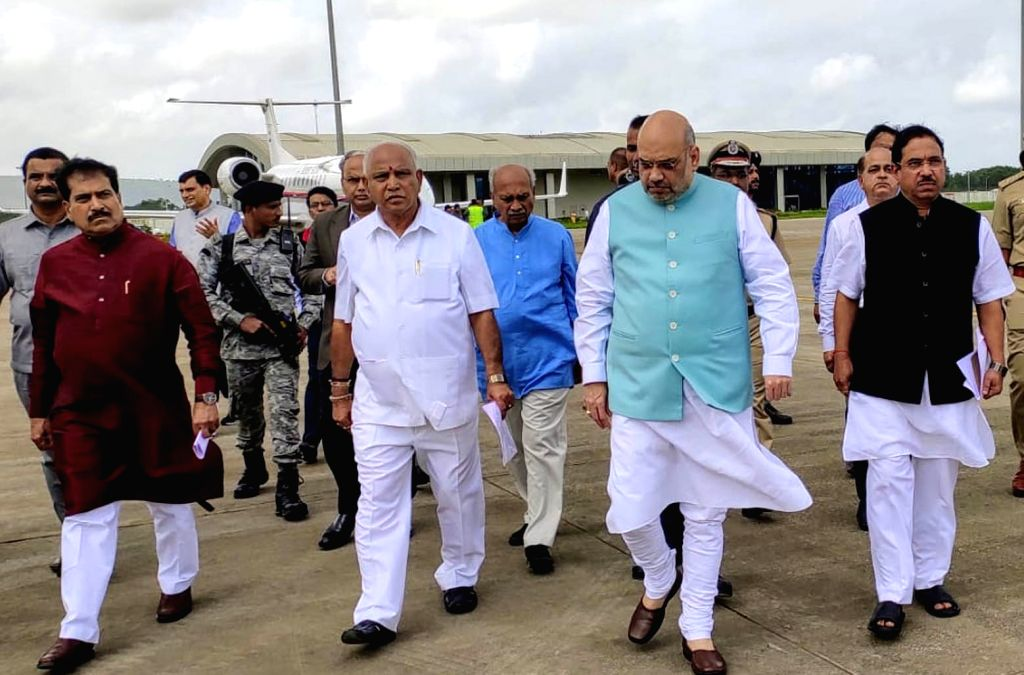 Belagavi: Union Home Minister Amit Shah arrives at a airport to make aerial survey flood affected area in Belagavi on Aug 11, 2019. Also seen Karnataka Chief Minister B.S. Yediyurappa. (Photo: IANS) - Amit Shah