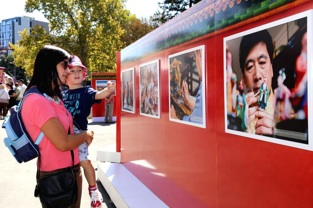 "BELGRADE, Sept. 16 Serbian citizens look at a photo exhibition presenting Chinese traditional culture during the event ""Days of Beijing in Belgrade"" at the Kalemegdan medieval ..."