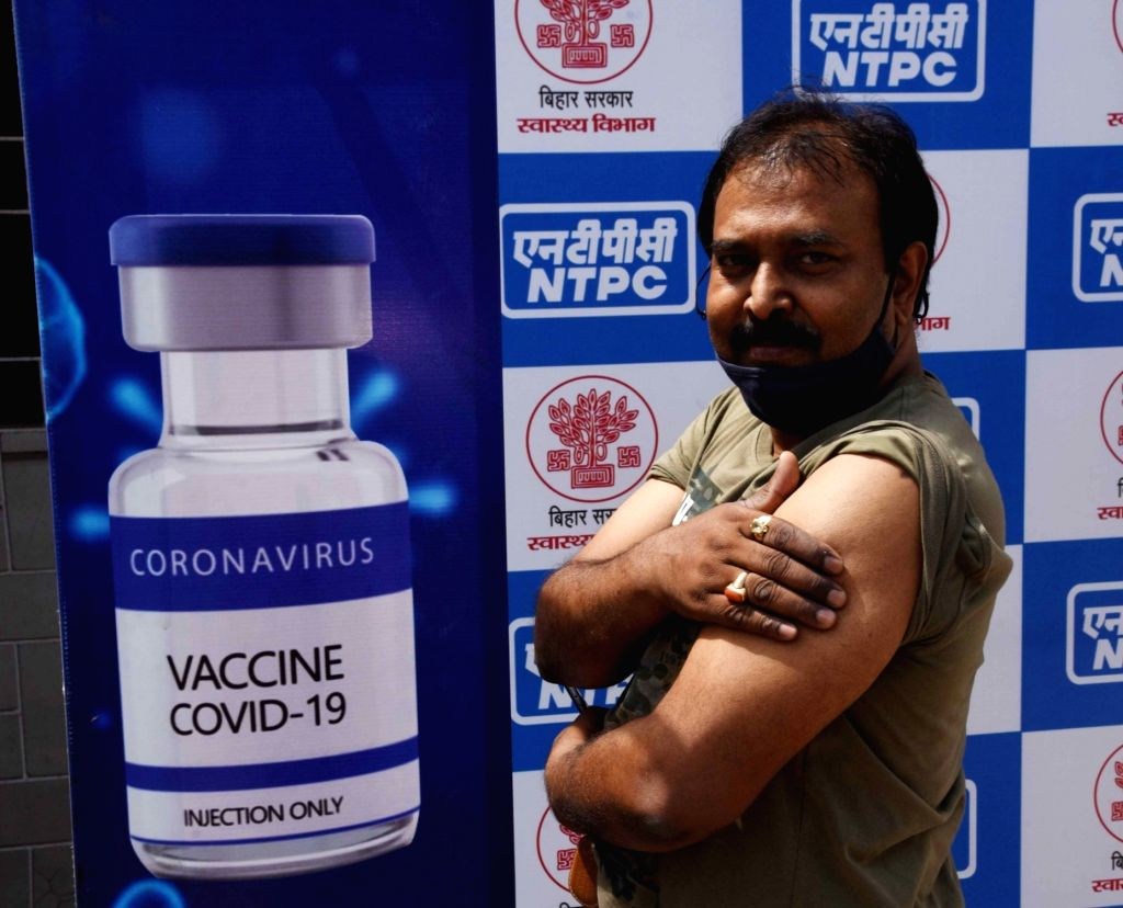 Beneficiary receives the first dose of COVID-19 vaccine during the third phase of the countrywide inoculation drive, amid coronavirus cases spike across the country, in Patna on Sunday, April ...