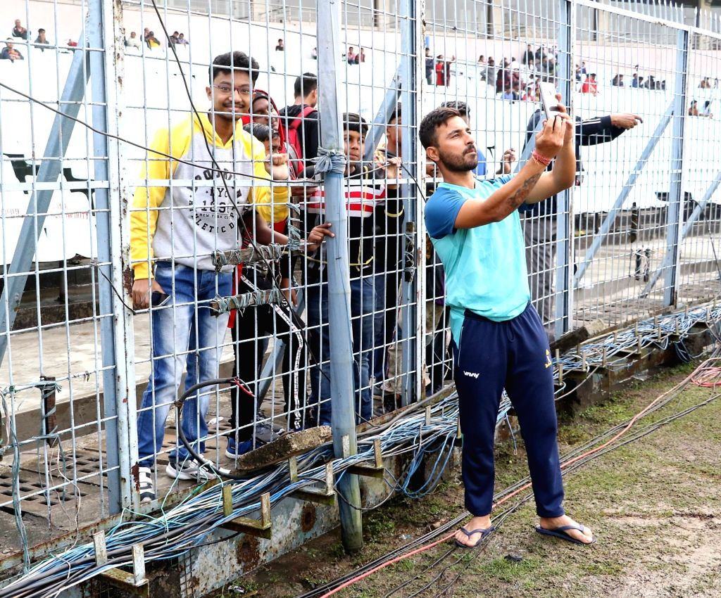 Bengal's Shreevats Goswami poses for selfies with fans during the Ranji Trophy match between Delhi and Bengal at the Eden Gardens in Kolkata on Jan 30, 2020. - Shreevats Goswami