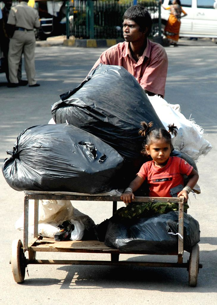 A child sits on a cart laded with scraps in Bengaluru on Jan 10, 2015.